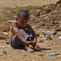One in a million: A Syrian boy sits on the ground at a temporary refugee camp in the eastern Lebanese town of Al-Faour, near the border with Syria, on Sept. 11 | AP