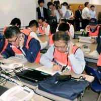 This is just a test: Ehime prefectural officials work the phones during a disaster drill for a radiation leak at the Ikata nuclear power plant in Ehime Prefecture | KYODO