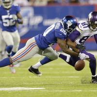 Dropping the ball: New York Giants cornerback Prince Amukamara (20) breaks up a pass to Minnesota Vikings Jerome Sipson (81) during an NFL game Monday. A recent study of NFL alumni showed 'profound abnormalities' in brain activity | AP