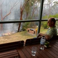 Blazing away: A man watches containment fires from the balcony of his home at Faulconbridge in the Blue Mountains, west of Sydney, on Tuesday. Firefighters deliberately merged two major blazes in New South Wales state in a desperate battle to manage the advancing infernos | AFP-JIJI