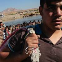 Refugees refused: Refugees turn back after being refused entry from northeast Syria into Iraq by the Kurdistan regional government Wednesday. The bridge crossing has been closed since the end of May, allowing through only humanitarian aid and those who are ill | AFP-JIJI