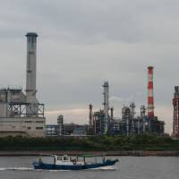 Full steam ahead: A work boat passes plants in the Keihin Industrial Area in Kawasaki on July 29 | BLOOMBERG