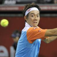 Successful start: Kei Nishikori hits a return against Jurgen Melzer on Tuesday in their first-round match at the Rakuten Japan Open. Nishikori defeated Melzer in three sets. | KYODO