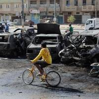 Never-ending detail: Baghdad municipal workers clear debris while citizens inspect the site of a car bomb attack in the Sha'ab neighborhood Sunday, after insurgents unleashed a new wave of bombings in Shiite neighborhoods in the Iraqi capital, killing and wounding dozens | AP