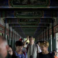 Picture perfect?: A tourist takes pictures as he and others walk down a corridor adorned with thousands of paintings depicting landscapes, birds and flowers at the Summer Palace in Beijing in August | AP