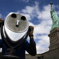 American icon: The Statue of Liberty looms over a visitor as he uses binoculars to look out over New York Harbor on Sunday. The statue was reopened to the public after New York state agreed to shoulder the costs of running the site during the partial federal government shutdown.   | AP