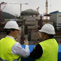 Atomic agreement: British Chancellor of the Exchequer George Osborne (left) chats with Taishan Nuclear Power Joint Venture Co. Ltd. General Manager Guo Liming as he inspects an atomic reactor under construction at a power plant in Taishan, southeastern China, on Thursday. Britain agreed Monday to build the country's first nuclear power plant in a generation, despite concerns raised by the Fukushima atomic crisis in Japan | AP