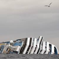 Salvage: A seagull flies over the partially submerged Costa Concordia on Jan. 16, 2012, off the coast of Giglio, Italy | AFP-JIJI