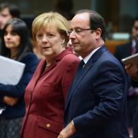 German Chancellor Angela Merkel and French President Francois Hollande arrive at the European Council meeting at the EU headquarters in Brussels on Thursday   AFP-JIJI