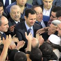 Position of power: Syrian President Bashar Assad (center) is greeted by supporters after prayers at a Damascus mosque on Oct. 15 | AFP-JIJI