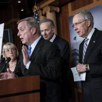 Crisis over, for now: Democratic Sens. Patty Murray (left), Charles Schumer (second from right) and Harry Reid, the chamber's majority leader, listen as Senate Democratic Whip Richard Durbin speaks to the press after senators passed legislation to compromise on budget and debt concerns to reopen the U.S. government | AFP-JIJI