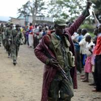 Conquering heros: A Congolese soldier responds to cheers from civilians Wednesday as the army enters the town of Bunagana, near the border with Uganda in the east | AP