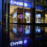 Chastened: Cars pass by a JPMorgan Chase building in New York in May 2012. JPMorgan said Friday it has agreed to pay $5.1 billion to resolve claims that it misled Fannie Mae and Freddie Mac about risky mortgage securities it sold them before the housing market collapsed | AP