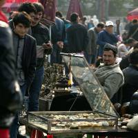 Targeted: Uighur jade vendors sell their wares Wednesday at an outdoor market where Chinese police have been checking their IDs daily since the deadly vehicle attack at Tiananmen Square in Beijing that killed five people Monday. Members of China's ethnic Uighur community in the city say they're facing stepped-up scrutiny following the incident | AP