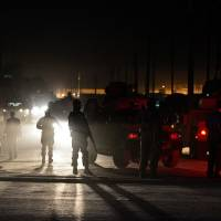 Truly bazaar: Afghan police guard the site of an attack by a Taliban suicide bomber on foreign troops in Kabul on Friday. As the U.S. troop withdrawal from the country and sell-off of equipment accelerates, the Taliban have become part of the world's biggest garage sale   AFP-JIJI