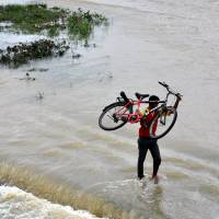 An Indian man carries his bicycle through the waters of the overflowing Swarnrekha river following heavy rains due to Cyclone Phailin  in the Ranchi district, capital of Jharkhand state, on Monday. | AFP