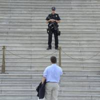 Impasse: A man speaks with police outside the U.S. Capitol in Washington on Tuesday, after the federal government largely shut down because Congress remains deadlocked over the budget and the Affordable Care Act. | THE WASHINGTON POST
