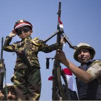 Fewer toys: An Egyptian boy in an army costume salutes while posing next to soldiers from atop an armored vehicle guarding an entrance to Cairo's  Tahrir Square on Sunday. | AP