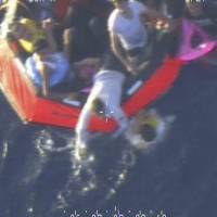 Desperate journey: This photograph provided by the Maltese Army shows migrants aboard a life raft after a boat carrying about 200 capsized off the Italian island of Lampedusa on Friday. | AP