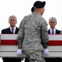 Defense Secretary Chuck Hagel (left) and Army Secretary John McHugh (right) watch as the remains of a soldier killed in Afghanistan are carried at Dover Air Force Base, in Delaware, last Wednesday. | AP, WIKIPEDIA