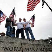 Battle lines drawn: Demonstrators watch from atop a wall as veterans accompanied by their families and supporters hold a rally Sunday at the World War II Memorial in Washington to protest its closure amid the U.S. government shutdown. | THE WASHINGTON POST