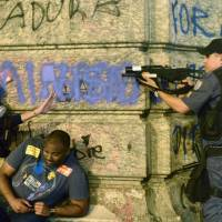 Taking aim: A police officer points a tear gas gun at demonstrators during protests over teachers' working conditions and police brutality on Tuesday in Rio de Janeiro. | AFP-JIJI