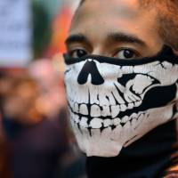 A bone to pick: An activist takes part in a protest demanding better working conditions and an end to police violence Tuesday in Rio de Janeiro. | AFP-JIJI
