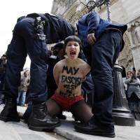 Activist anger: A member of the feminist activist group Femen is arrested by police after a May protest inside Notre Dame Cathedral in Paris.   AFP-JIJI