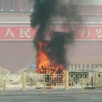 Unlawful behavior: A vehicle bursts into flames after crashing into one of the ancient stone bridges leading to the Tiananmen Gate in Beijing on Oct. 28. | KYODO