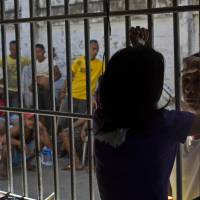 Not barred from love: A prisoner is visited by a woman through the bars of the Tacloban City Prison in the Philippine city of Tacloban on Monday. | AP