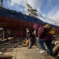 Survival tales: Two women pass by a ship that was washed into their neighborhood by the tsunami as they search for their destroyed home in the leveled city of Kesennuma, in northeastern Japan, March 17, 2011.   AP