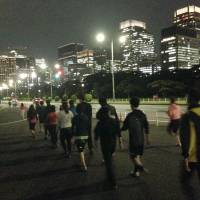 Love on the run: Men and women who are participating in a jogging matchmaking party chat as they make their way around Tokyo's Imperial Palace in October. | JUN HONGO