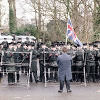 Brit in their midst: A lone loyalist carrying the Union Jack faces Royal Ulster Constabulary officers on the road leading to Stormont, near Belfast, in 1985.  Briton  Tim Burt was detained by the RUC in the 1980s and by  Tokyo's finest 30 years later. | AP