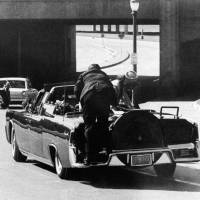 Moment of disbelief: Secret Service agent Clint Hill leaps aboard the rear deck of John F. Kennedy's limousine immediately after the president was fatally shot in Dallas on Nov. 22, 1963. | AP