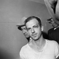 Lee Harvey Oswald is escorted through the Dallas police station on Nov. 23, 1963. Oswald would be gunned down by Jack Ruby the next day. | AP