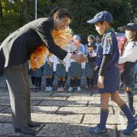 Prime Minister Shinzo Abe receives flowers from a child at ise Shrine, Mie Prefecture, in January. | KYODO
