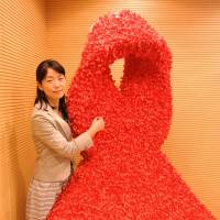 A SHARE employee adds a red ribbon containing a message of support for HIV sufferers at Sunstar headquarters in Tokyo. | PHOTO COURTESY OF NGO SHARE/SUNSTAR INC.