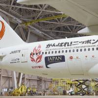 Games face: A Japan Airlines Boeing 777-200 sports messages to cheer on Japanese athletes who will compete in the Sochi Olympics next year. The special jet, seen Wednesday in a hangar at Tokyo's Haneda airport, started domestic service Thursday. | KYODO