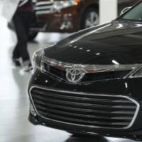 Motoring on: A visitor looks at Toyota Motor Corp.'s Avalon (front) and Venza models at the company's Tokyo showroom Tuesday. | BLOOMBERG
