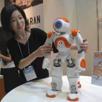 Here and NAO: Mai Miyazaki of Aldebaran Robotics demonstrates NAO, a humanoid robot equipped with a microphone, camera, speakers and motors to control limb and finger movements. NAO can speak 19 languages, get back up after falling over, and even remember human faces, according to the manufacturer. | ATSUSHI KODERA