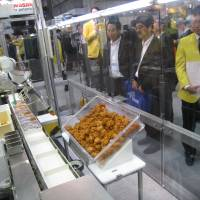 'Bento' bot: Visitors to Fanuc Corp.'s booth observe a demonstration by a robot arm developed by the company for filling 'bento' boxed meals at the International Robot Exhibition at Tokyo Big Sight on Thursday. The robot arm can grab a piece of fried chicken without crushing it and place it precisely in the right slot of a bento box. | ATSUSHI KODERA