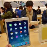 Must-have: Customers look over Apple's new iPad Air tablets at an Apple store in Tokyo on Friday. More than 300 customers lined up to buy the slimmed-down device, which debuted worldwide.   AFP-JIJI