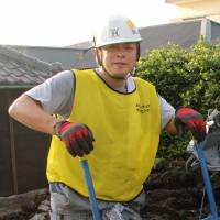 Muck raker?: Radio DJ Kosaku Mukai scoops mud out of damaged houses on Izu-Oshima Island last month. | KYODO