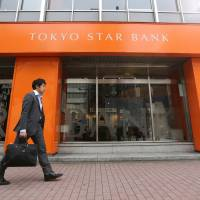 Acquired: A pedestrian walks past a Tokyo Star Bank Ltd. branch in Tokyo on April 10. | BLOOMBERG