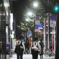 On guard: Police officers carry out a night patrol in Kitakyushu on Oct. 28. Mob violence in Fukuoka has been declining since the revised law against organized crime took effect in 2012. | KYODO