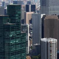 Office space: Commercial and residential buildings are seen from the observatory of the Mori Building Co.-operated Roppongi Hills Mori Tower on Sept. 3. The office vacancy rate in Tokyo fell in October to its lowest level in more than four years. | BLOOMBERG