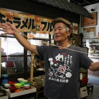 Old master: Yoshihito Fujita demonstrates a spinning top technique at his home-turned-museum in Nagoya. | CHUNICHI SHIMBUN