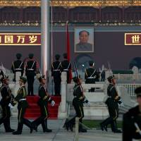 Nothing to see here: Chinese paramilitary police march during a flag-lowering ceremony in Tiananmen Square as security is increased Friday on the eve of an important Communist Party Congress in Beijing. | AFP-JIIJI