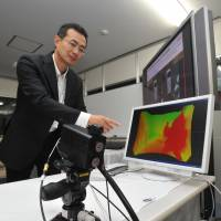 Masami Mizutani a research manager, explains laser radar technology that works with exterior cameras for cars. | YOSHIAKI MIURA