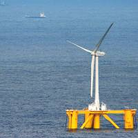 Breezing up: The first wind turbine in an experimental project floats on the sea some 20 km off the coast of Naraha, Fukushima Prefecture, on Monday. In the background is the Fukushima No. 2 nuclear power plant. | KYODO